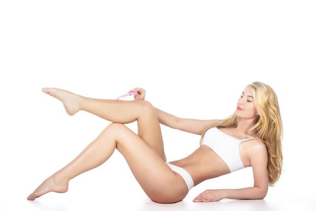 Isolé sur fond blanc. femme épilation des jambes avec un rasoir. femme se rasant les jambes dans la salle de bain. rasage des jambes. concept de spa, d'épilation et de soins du corps. jambes de fille en bonne santé le rasant soigneusement