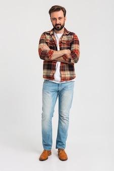 Isolé souriant bel homme barbu en tenue de hipster habillé en jeans