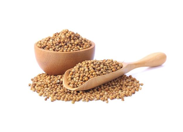 Isoler les graines de coriandre en morceaux dans une coupe en bois et une cuillère sur un fond blanc.