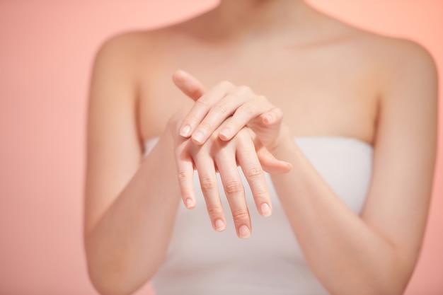 Isoler les mains de belles femmes, appliquer de la crème, masser