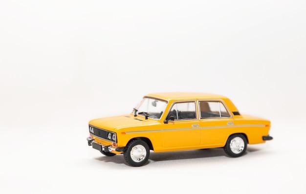 Isoler le modèle de jouet d'une voiture rétro jaune sur fond blanc