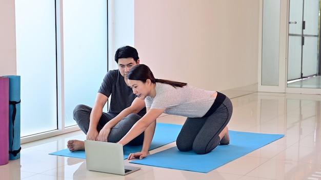 J'adore les couples en ligne apprenant le yoga, la respiration et la méditation ensemble à la maison. sport et exercice pour la santé. mode de vie asiatique de femme et d'homme.