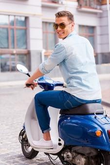 J'adore mon nouveau scooter ! vue arrière du jeune homme gai dans des lunettes de soleil équitation scooter le long de la rue et regardant par-dessus l'épaule