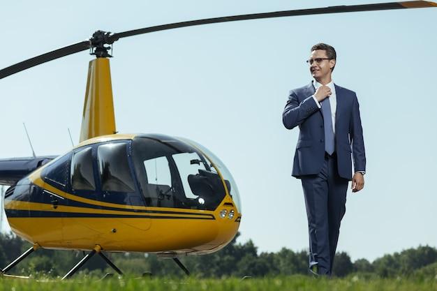 J'adore mon travail. beau jeune agent spécial posant près d'un hélicoptère sur un héliport et ajustant sa cravate en souriant