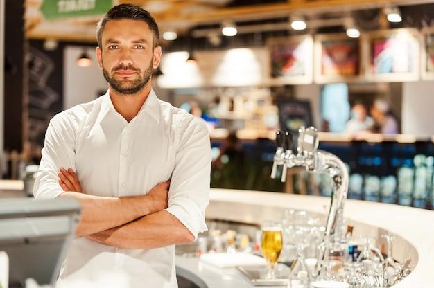 J'adore mon travail! jeune barman confiant gardant les bras croisés et regardant la caméra en se tenant debout au comptoir du bar