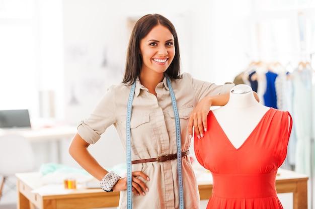J'adore mon travail! souriante jeune femme se penchant sur le mannequin avec une robe en se tenant debout dans son atelier de mode