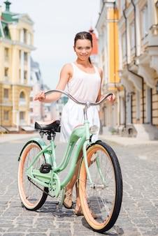 J'adore mon vélo vintage ! toute la longueur d'une jeune femme souriante séduisante, debout près de son vélo dans la rue