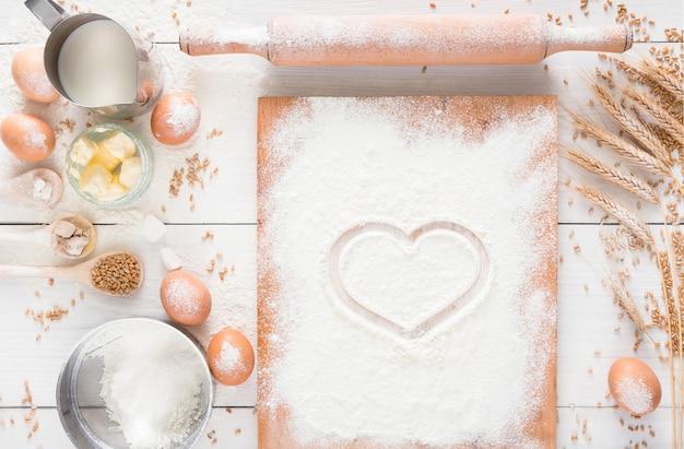 J'adore la pâtisserie. ingrédients de cuisson pour pâte à levure et pâtisserie, œufs, beurre et planche saupoudrée de farine, vue du dessus