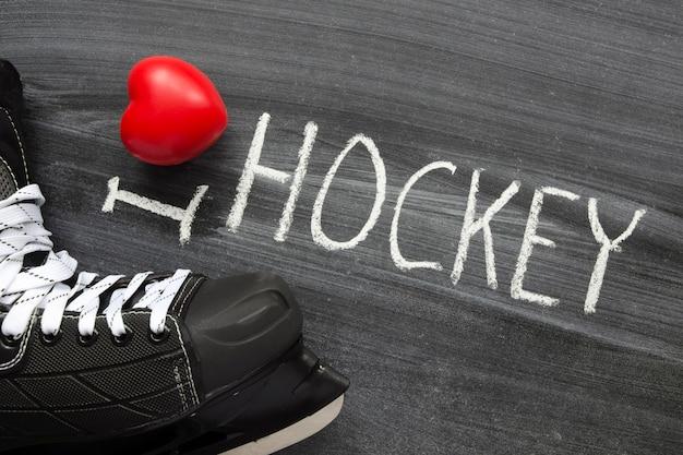 J'adore la phrase de hockey manuscrite sur le tableau noir de l'école avec des patins et le symbole du cœur rouge
