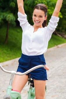 J'adore rouler ! heureuse jeune femme faisant du vélo et gardant les bras levés
