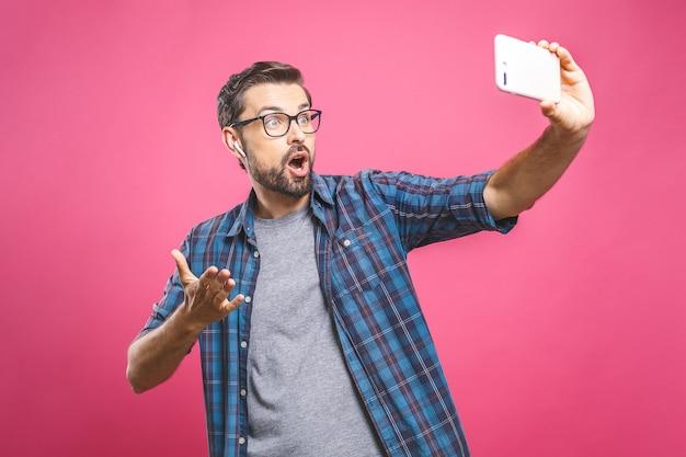J'adore le selfie! beau jeune homme en chemise tenant la caméra et faisant selfie et souriant. écouter de la musique avec des écouteurs.