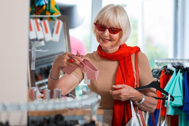 J'ai l'air mignon. tour de taille de femme aux cheveux gris heureux debout dans un magasin tout en tenant un bandeau à la main et en exprimant son intérêt