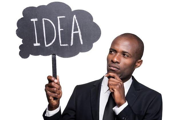 J'ai besoin d'une nouvelle idée. gentil jeune homme africain en tenue de soirée tenant une bannière avec du texte et le regardant en se tenant debout isolé sur fond blanc