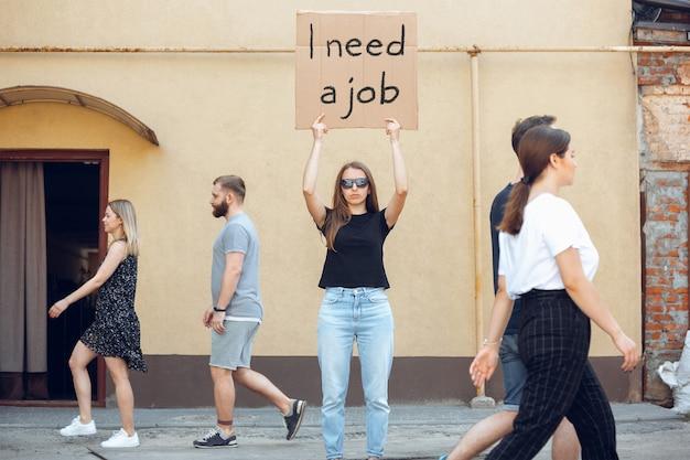 J'ai besoin d'un travail. mec avec signe - la femme se tient debout pour protester contre les choses qui l'ennuient. démonstration solo droit de parler gratuitement dans la rue avec signe. opinion entendue par le public. vie sociale, travail, finances.