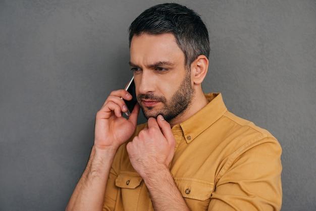 J'ai besoin d'y réfléchir. homme mûr réfléchi parlant au téléphone portable et tenant la main sur le menton tout en se tenant sur le fond gris