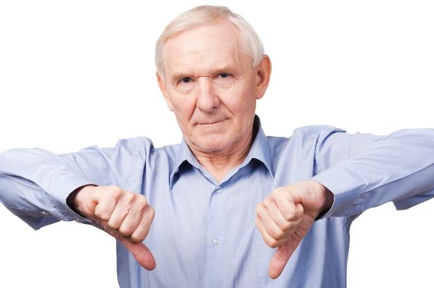 J'ai dit non! homme senior sérieux en chemise montrant ses pouces vers le bas et regardant la caméra en se tenant debout sur fond blanc