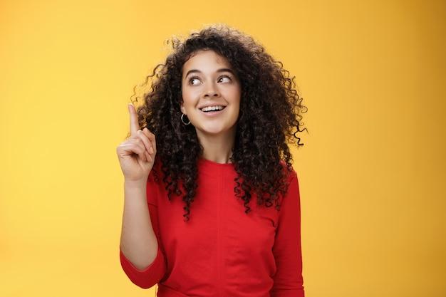 J'ai eu l'idée excitée heureuse jolie femme aux cheveux bouclés en robe rouge levant l'index en eurek...