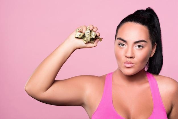 J'en ai marre. gros plan d'une fille mulâtre en colère debout contre un mur rose isolé et tenant un ruban à mesurer de corps froissé.