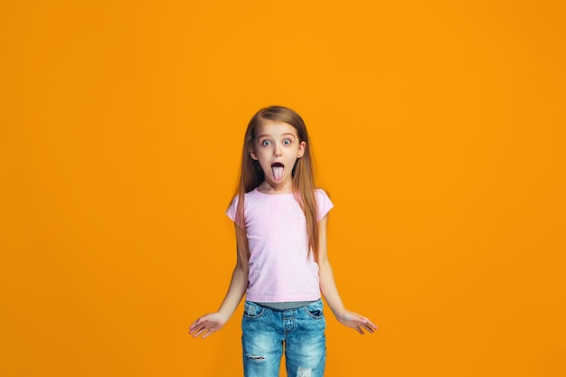 J'ai perdu la tête. l'adolescente à l'expression étrange. beau portrait de demi-longueur féminin isolé sur fond de studio orange. l'adolescent fou. les émotions humaines, concept d'expression faciale.