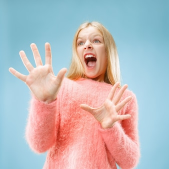J'ai peur. la frayeur. portrait de l'adolescente effrayée. elle debout isolée sur fond de studio bleu à la mode. portrait de femme demi-longueur.