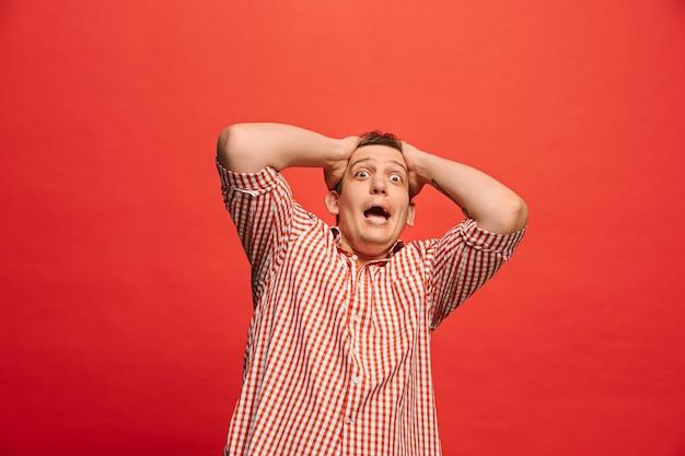 J'ai peur. la frayeur. portrait d'homme effrayé. homme d'affaires debout isolé sur rouge à la mode. portrait demi-longueur mâle