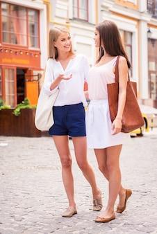 J'ai tellement de choses à te dire! deux belles jeunes femmes marchant le long de la rue et parlant
