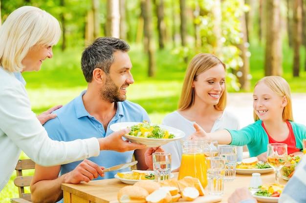 J'ai tellement faim ! héhé, savourant un repas ensemble pendant qu'une femme âgée passe une assiette avec de la salade à une petite fille