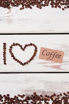 J'aime le café fait de grains et de papier avec word. planches de bois blanches. mise à plat.