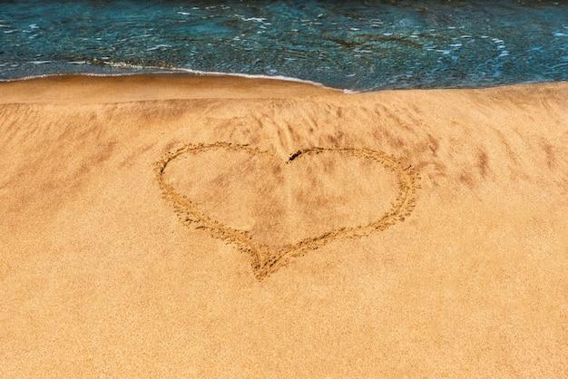 J'aime l'été. coeur dessiné sur la plage, sur le sable