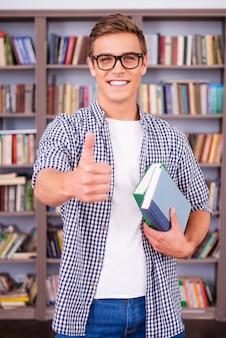 J'aime étudier! heureux jeune homme tenant des livres et montrant son pouce en se tenant debout dans la bibliothèque