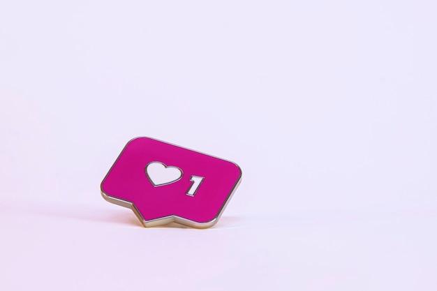 J'aime l'icône du réseau social. icône rose avec un coeur sur fond clair.