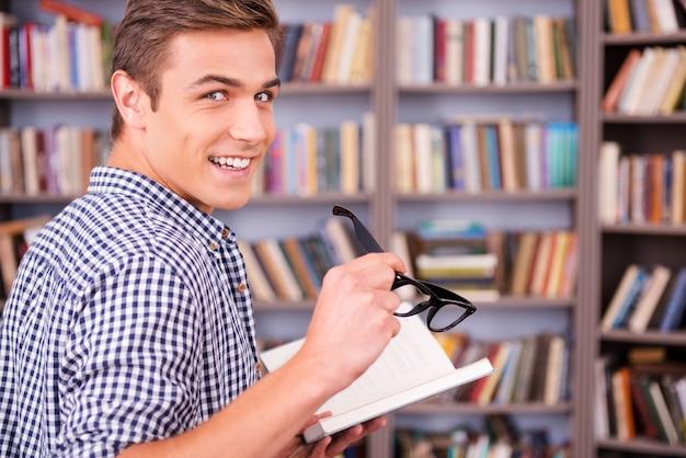 J'aime lire! vue arrière d'un jeune homme heureux tenant un livre et regardant par-dessus l'épaule en se tenant debout contre une étagère