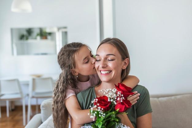 J'aime ma toi maman! une jeune femme séduisante avec une petite fille mignonne passe du temps ensemble à la maison, remerciant pour la carte faite à la main avec le symbole de l'amour et les fleurs. notion de famille heureuse. fête des mères.