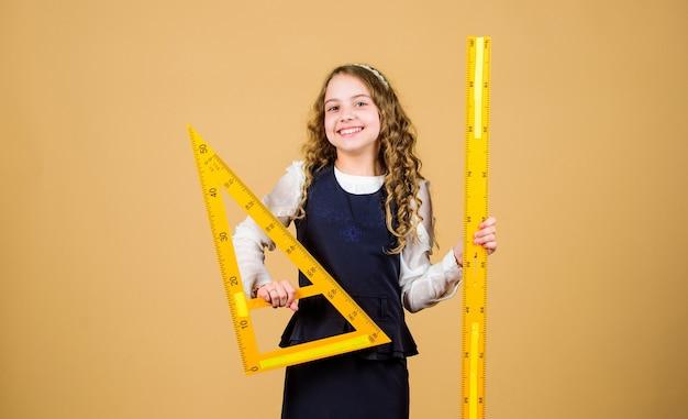 J'aime les mathématiques. concept d'éducation et d'école. concept intelligent et intelligent. dimensionnement et mesure. élève jolie fille avec une grande règle. l'élève de l'école étudie la géométrie. l'uniforme scolaire pour enfants tient la règle.