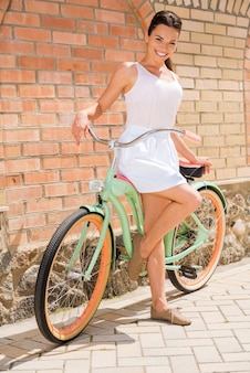 J'aime mon vélo! toute la longueur de la jolie jeune femme souriante debout près de son vélo vintage