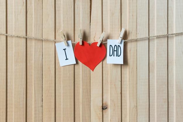 J'aime papa. notion de fête des pères. message avec coeur de papier suspendu avec des épingles sur une planche de bois clair.