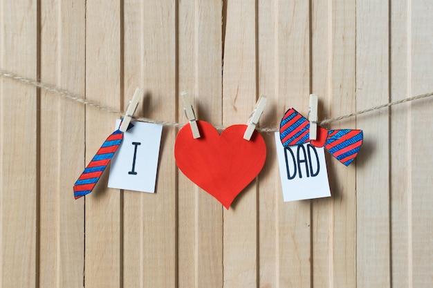 J'aime papa. notion de fête des pères. message avec coeurs de papier, cravate et noeud papillon suspendus avec des épingles sur une planche de bois clair.