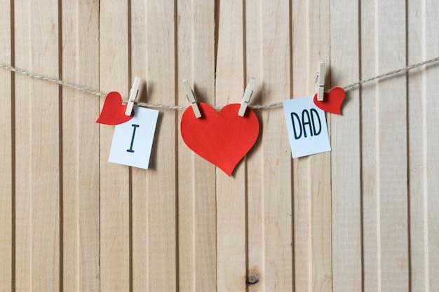 J'aime papa. notion de fête des pères. message avec des coeurs de papier suspendus avec des épingles sur une planche de bois clair.