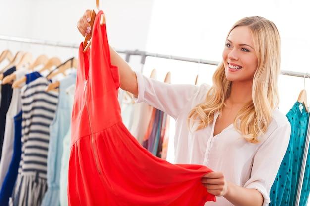 J'aime cette robe! souriante jeune femme tenant une robe et souriante en se tenant debout dans un magasin de vêtements