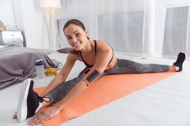 J'aime le sport. belle jeune femme aux cheveux noirs athlétique exubérante souriant et exerçant tout en étant assis sur le tapis
