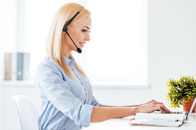 J'aimerais vous aider ! vue latérale d'une belle jeune femme joyeuse dans un casque travaillant sur un ordinateur portable et souriante assise sur son lieu de travail