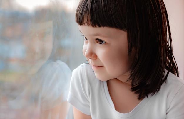 J'espère qu'une petite fille à la maison regarde à travers la vitre.