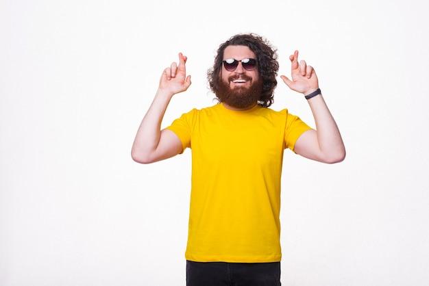J'espère que ça ira. homme barbu portant des lunettes de soleil croise les doigts.