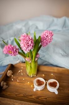 Jacinthes roses dans un vase et café