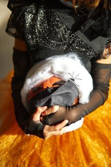 Jack o lantern, citrouille d'halloween en masque noir de protection médicale dans les mains de la fille lors de la célébration d'halloween à la maison pandémie de coronavirus covid19, espace de copie