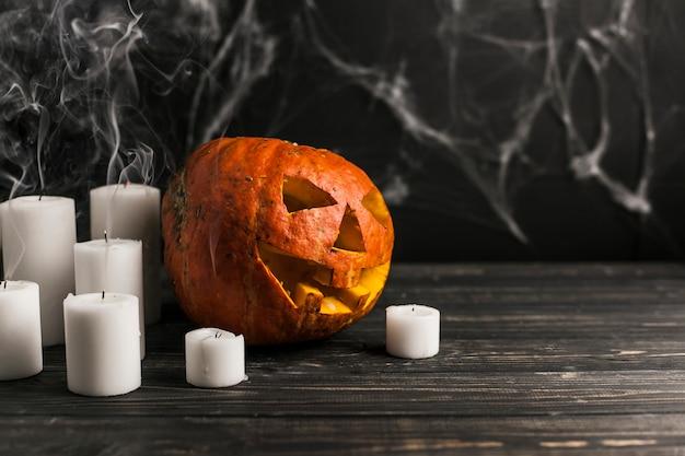 Jack-o-lantern sculpté et bougies blanches