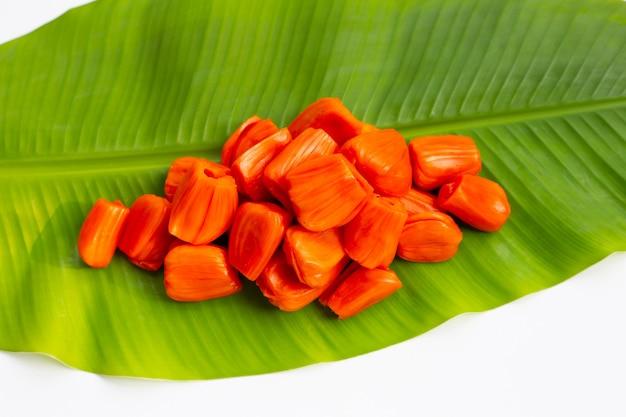 Jacquier rouge mûr sur feuille de bananier sur une surface blanche