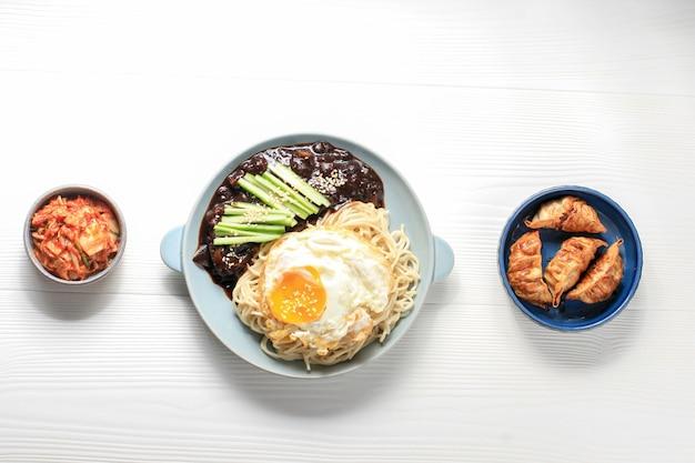 Jajang myeon ou nouilles coréenne jjajangmyeon avec sauce aux haricots noirs, servies avec concombre et graines de sésame
