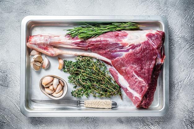 Jambe de chèvre ou d'agneau crue non cuite aux herbes dans une plaque à pâtisserie.