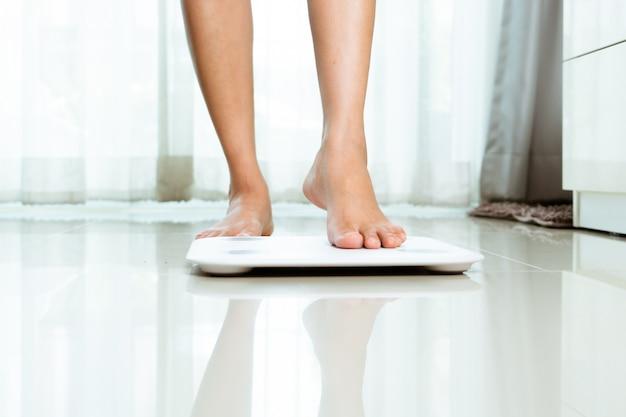 La jambe féminine marche sur des écailles blanches à la maison
